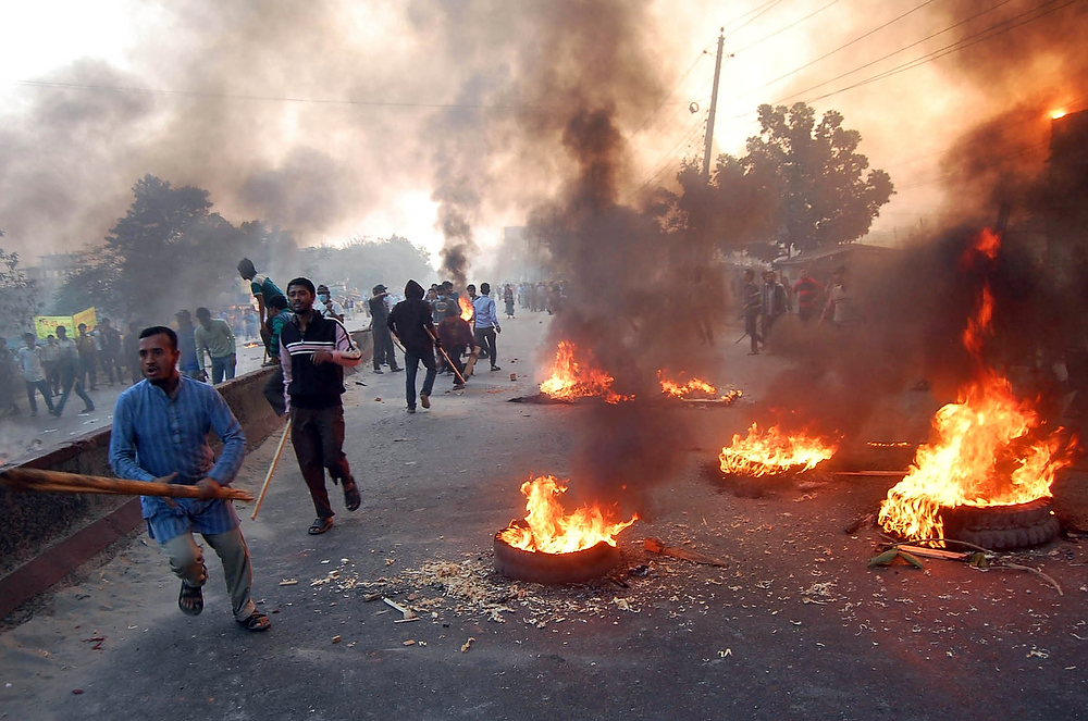 Description of . Bangladesh's largest Islamic party Jamaat-e-Islami activists block a road with burning tires during a nationwide strike on the outskirts of Dhaka, Bangladesh, Tuesday, Dec. 4, 2012. The opposition Jamaat-e-Islami party called the strike to demand authorities halt trials of its top leaders on charges of crimes against humanity during the 1971 independence war against Pakistan. (AP Photo)