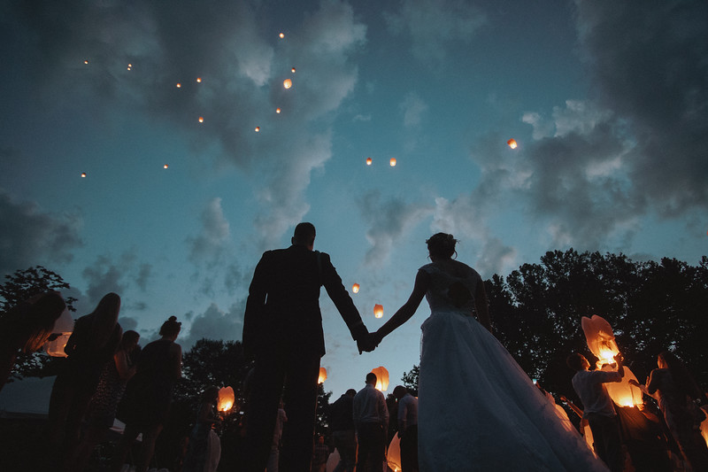 The bride and groom hold hands as they watch lanterns fill the sky.