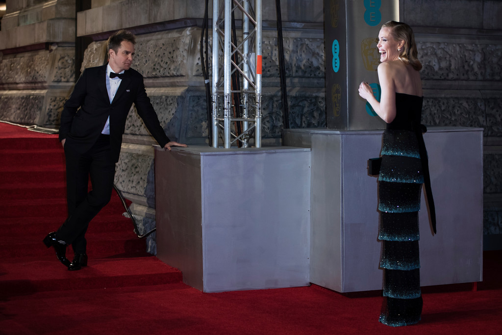 . Actor Sam Rockwell, left, watches partner Leslie Bibb as she poses for photographers upon arrival at the BAFTA Awards 2018 in London, Sunday, Feb. 18, 2018. (Photo by Vianney Le Caer/Invision/AP)