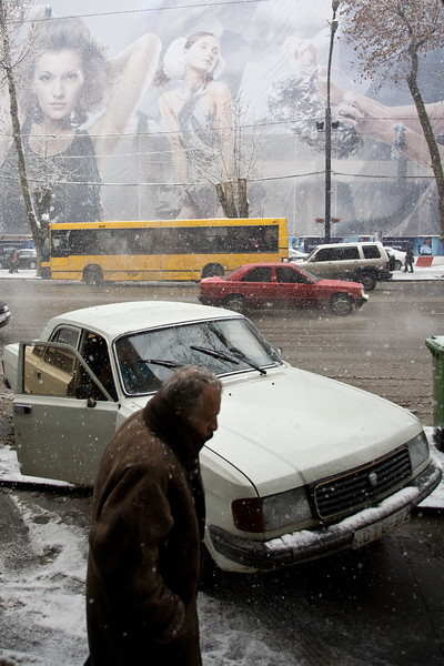 Tbilisi, Georgia - January, 2008:A old soviet car on Rustavelis street in Tbilisi with  Fashion models advertising a new building construction in the background. (Photo by Christopher Herwig)