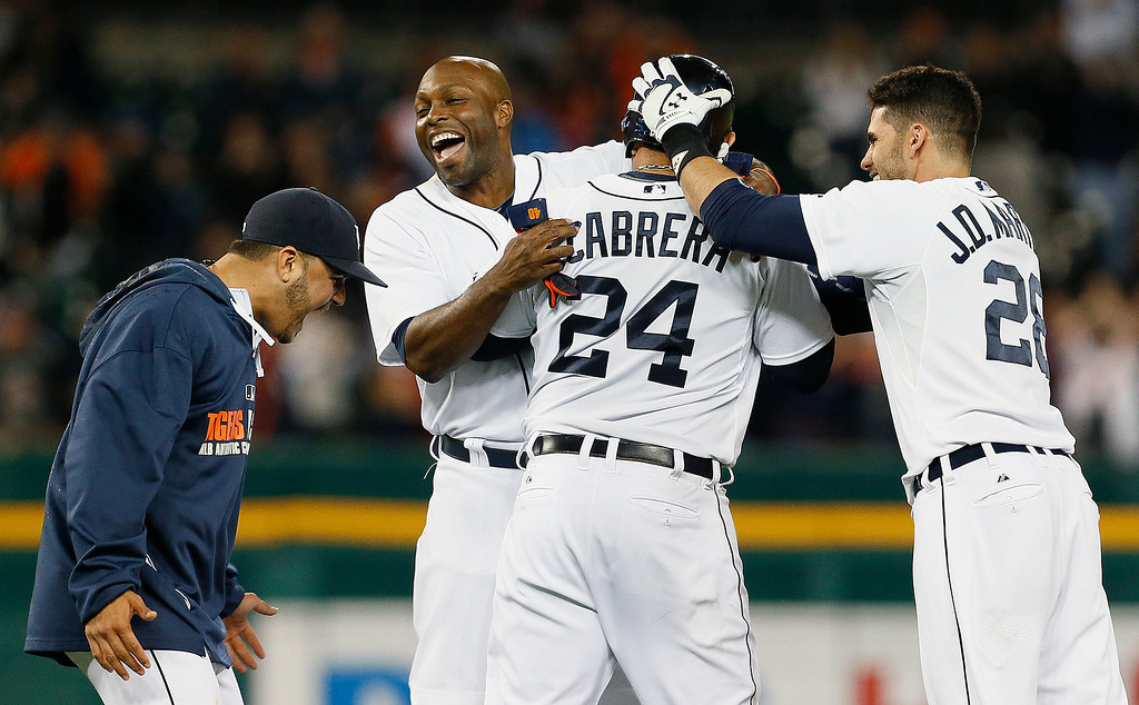 . Detroit Tigers first baseman Miguel Cabrera (24) celebrates after hitting a walk off one-run single against the Chicago White Sox with Eugenio Suarez, left, Torii Hunter and J.D. Martinez (28) in the ninth inning of a baseball game in Detroit Tuesday, Sept. 23, 2014. Detroit won 4-3. (AP Photo/Paul Sancya)