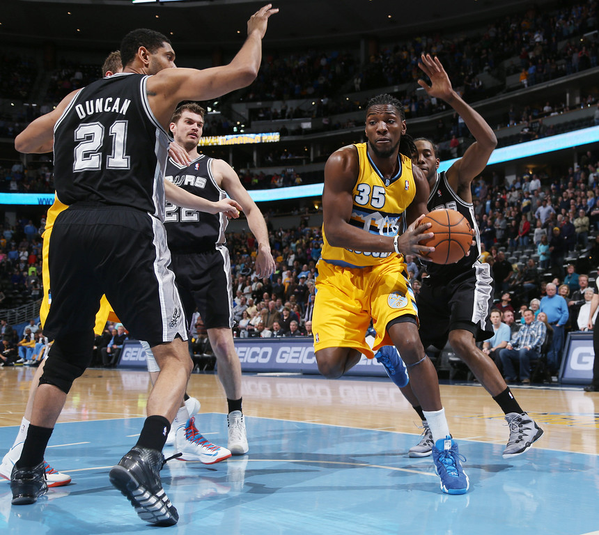 . Denver Nuggets forward Kenneth Faried, front right, picks up a loose ball in the lane as, from left, San Antonio Spurs center Tim Duncan and forwards Tiago Splitter, of Brazil, and Kawhi Leonard cover in the first quarter of an NBA basketball game in Denver, Friday, March 28, 2014. (AP Photo/David Zalubowski)