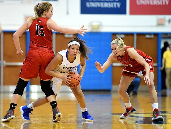 1/19/2019 Mike Orazzi | Staff CCSU's Kiana Patterson (4) and Saint Francis University's Haley Thomas (15) and Sam Sabino (13) during Saturday's basketball game in New Britain.