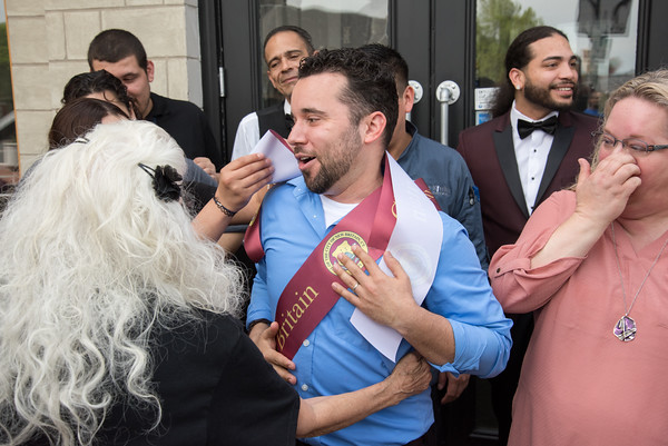 05/17/18 Wesley Bunnell | Staff Vincent Placeres held a ribbon cutting for his newest restaurant The Kitchen on Thursday afternoon down the street from Mofongo Restaurant which he opened in 2017. Placeres wraps himself in ribbon just after the ceremony as he is congratulated by family, friends, and city officials.