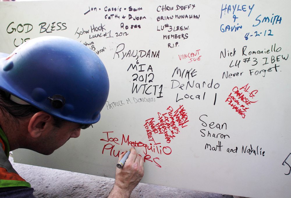 ". In this Aug. 2, 2012 file photo, a construction worker signs a ceremonial steel beam at One World Trade Center in New York. The beam was signed by President Barack Obama with the notes: ""We remember,\"" \'\'We rebuild\"" and \""We come back stronger!\"" during a ceremony at the construction site June 14. The beam, having since adorned with the autographs of workers and police officers at the site, will be sealed into the structure of the tower, which is scheduled for completion in 2014. (AP Photo/Mark Lennihan, File)"