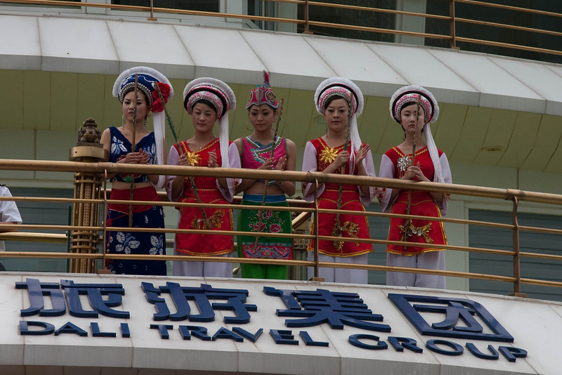 Bai girls singing before the tourists embark on the cruise ship.