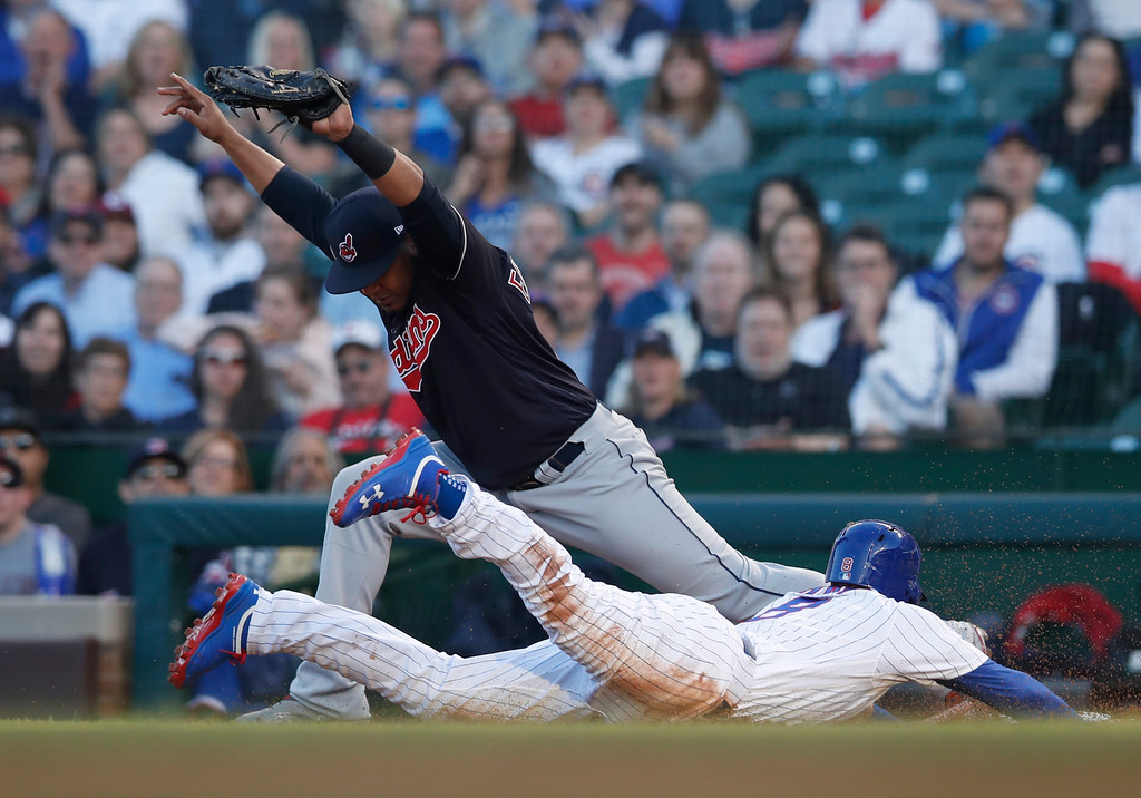 . Chicago Cubs\' Ian Happ dives back to first base but is out as Cleveland Indians\' Edwin Encarnacion touches the base for the second out of a double play during the first inning of a baseball game Wednesday, May 23, 2018, in Chicago. (AP Photo/Jim Young)