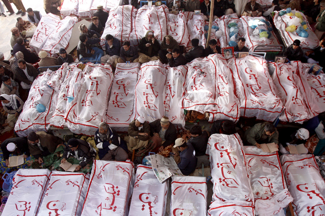 """. Pakistani Shiite Muslims sit in protest next to the dead bodies of their family members killed in Saturday\'s bombing, in Quetta on Monday, Feb. 18, 2013. The protesters have refused to bury victims of the attack until authorities take action against the militants who were responsible. Writing on shrouds reads, \""""We are ready Hussain.\"""" (AP Photo/Arshad Butt)"""