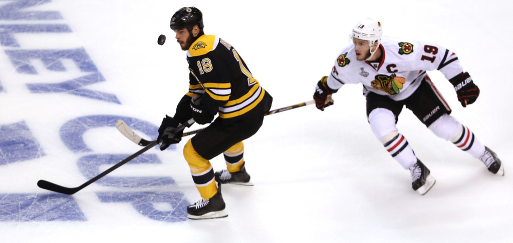 . Nathan Horton #18 of the Boston Bruins goes for a loose puck against Jonathan Toews #19 of the Chicago Blackhawks during the first period in Game Four of the 2013 NHL Stanley Cup Final at TD Garden on June 19, 2013 in Boston, Massachusetts.  (Photo by Bruce Bennett/Getty Images)