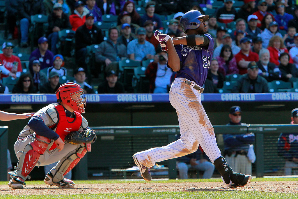 . Colorado Rockies\' Dexter Fowler (24) hits an RBI double to score Troy Tulowitzki and Jonathan Herrera during the ninth inning of a baseball game against the Atlanta Braves, Wednesday, April 24, 2013, in Denver. The Rockies won 6-5 in the 12th inning. (AP Photo/Barry Gutierrez)