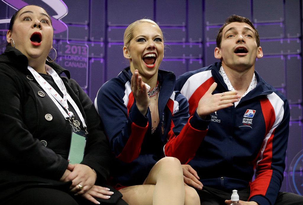 . Alexa Scimeca and Chris Knierim, of the United States, with their coach Dalilah Sappenfield, left, react as they watch their scores during the pairs free program at the World Figure Skating Championships Friday, March 15, 2013, in London, Ontario. (AP Photo/Darron Cummings)