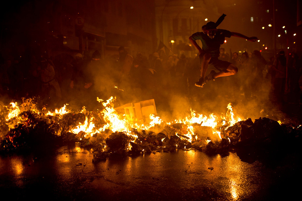 . A demonstrator with his face covered jumps over a burning barricade at the Cinelandia square during a march in support of teachers on strike in Rio de Janeiro, Brazil, Monday, Oct. 7, 2013. (AP Photo/Felipe Dana)