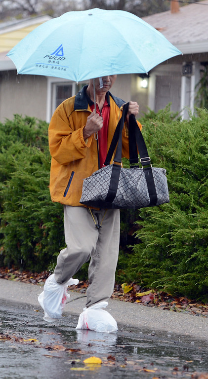 . Repurposed plastic grocery bags serve as a pair of galoshes for this man who braves the wet weather along Jeffrey Drive in Pleasant Hill, Calif., Thursday, Dec. 11, 2014. (Susan Tripp Pollard/Bay Area News Group)