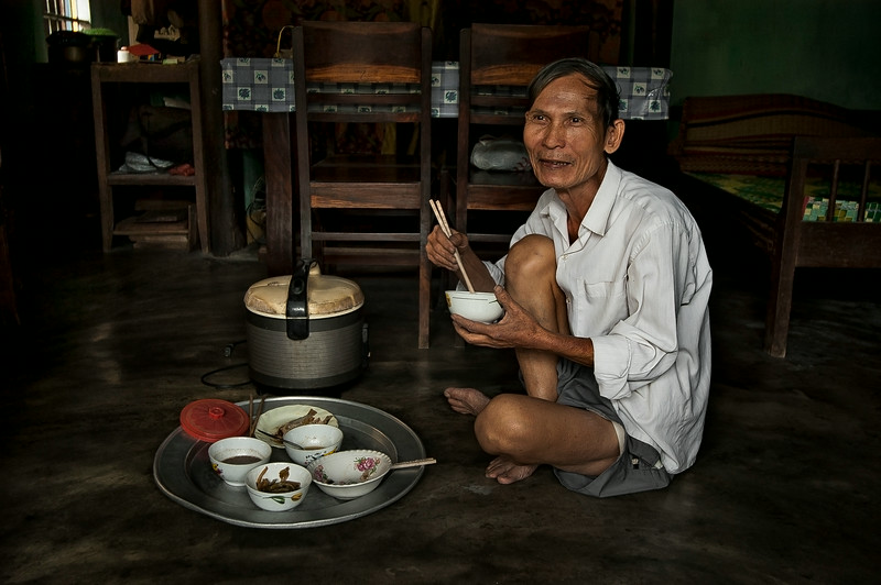 Although many homes have chairs and tables, most still prefer to eat the traditional way by sitting on the floor.   Hoi An, Vietnam, 2008