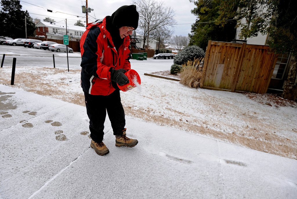 . University of Mississippi Landscaping Services employee Paul Stowe sprinkles salt on sidewalks to thaw the ice on the campus in Oxford, Miss., Tuesday, Feb. 11, 2014. There is another chance of snow or sleet in northern Mississippi for Tuesday night, with low temperatures in the low to mid-twenties. Mississippi Gov. Phil Bryant declared a state of emergency Monday ahead of the winter storm. The declaration cleared the clearing the way for state officials to move quickly to respond to problems that could be created by snow or ice. (AP Photo/The Daily Mississippian, Thomas Graning)
