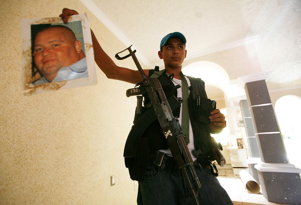 . A young man, who identifies himself as M3, holds up a photo of what he claims is a businessman sympathizing and aiding the Templar Knights cartel inside the alleged home of a Templar Knight member in the town of Aguililla, Mexico, Thursday, July 25, 2013. The 18-year-old, who claims on a video posted on a national newspaper website, that he is a former Templar Knights gunman who deserted the cartel and joined the ranks of the Aguililla self-defense group because he was disgusted with the way the Templar Knights treat the community. (AP Photo/Gustavo Aguado)