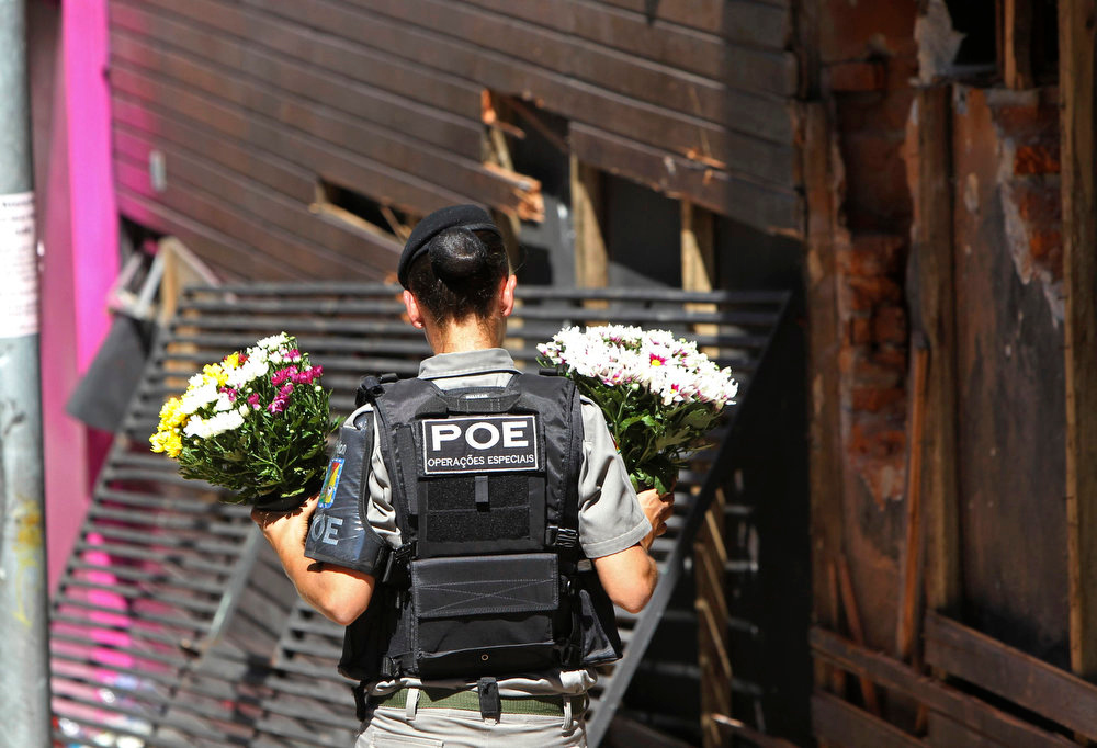 Description of . A policewoman carries flowers to place in front of the Boate Kiss nightclub in the southern city of Santa Maria, 187 miles (301 km) west of the state capital Porto Alegre, January 28, 2013. The Boate Kiss nightclub fire killed at least 233 people in southern Brazil on Sunday when a band's pyrotechnics show set the building ablaze and fleeing partygoers stampeded toward blocked exits in the ensuing panic, officials said. REUTERS/Edison Vara