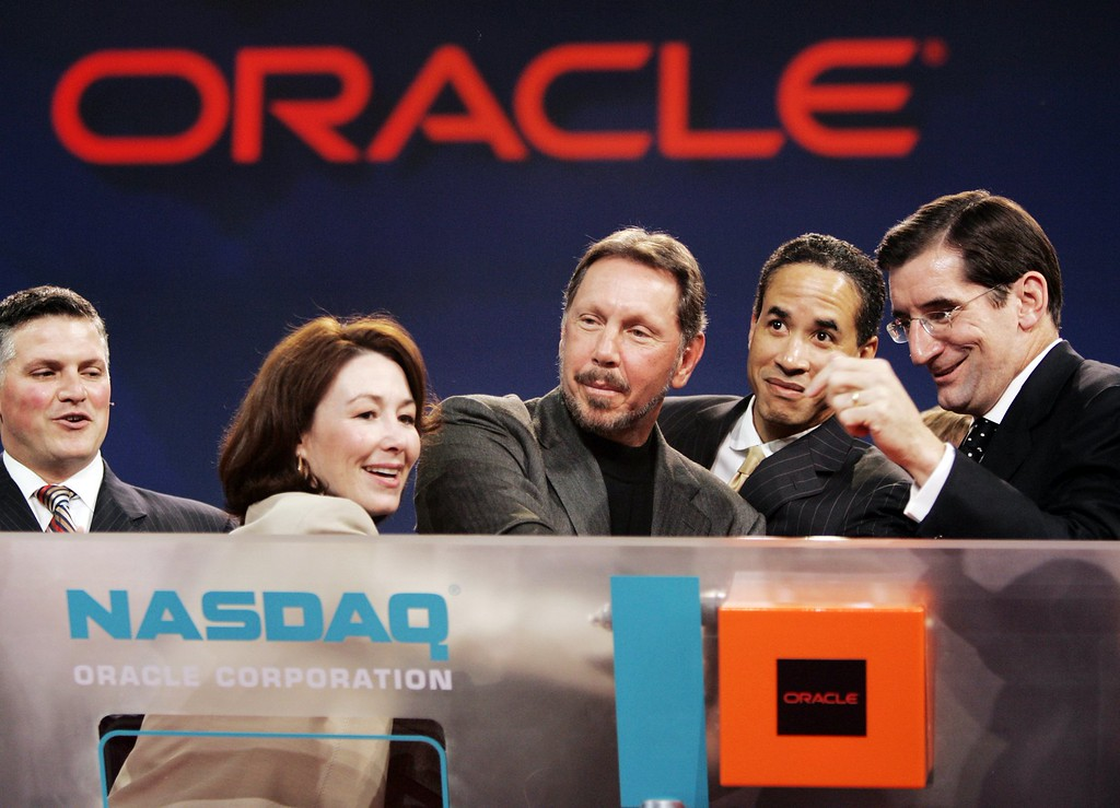 . Oracle CEO Larry Ellison, center is surrounded by Oracle and Nasdaq officials, Oracle CFO Safra Catz, second left, Oracle president Charles Phillips, center right, and Nasdaq CEO Robert Greifeld, right, as he closes the Nasdaq before his keynote address at Oracle Open World conference in San Francisco, Wednesday, Oct. 25, 2006. Man at left is unidentified. (AP Photo/Paul Sakuma)