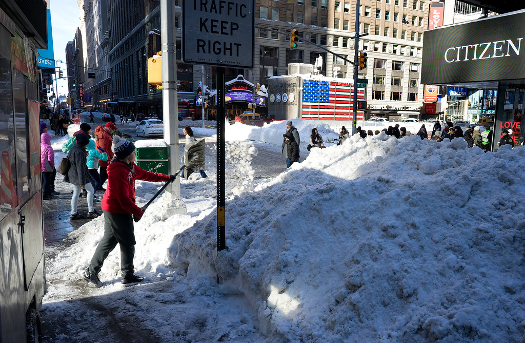 . Snow is cleared near a street vendor\'s location on New York\'s Times Square Sunday, Jan. 24, 2016, in the wake of a storm that dumped heavy snow along the East Coast. (AP Photo/Craig Ruttle)