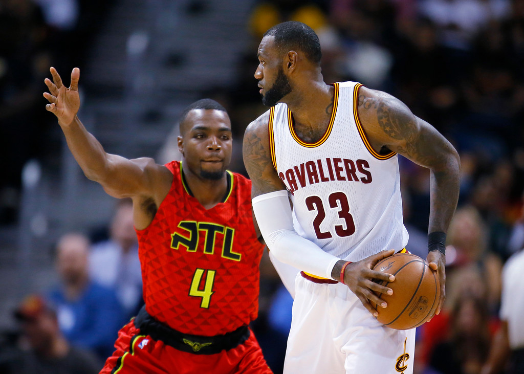 . Cleveland Cavaliers forward LeBron James (23) is defended by Atlanta Hawks forward Paul Millsap (4) in the first half of an NBA basketball game on Sunday, April 9, 2017, in Atlanta. The Hawks won in overtime 126-125. (AP Photo/Todd Kirkland)