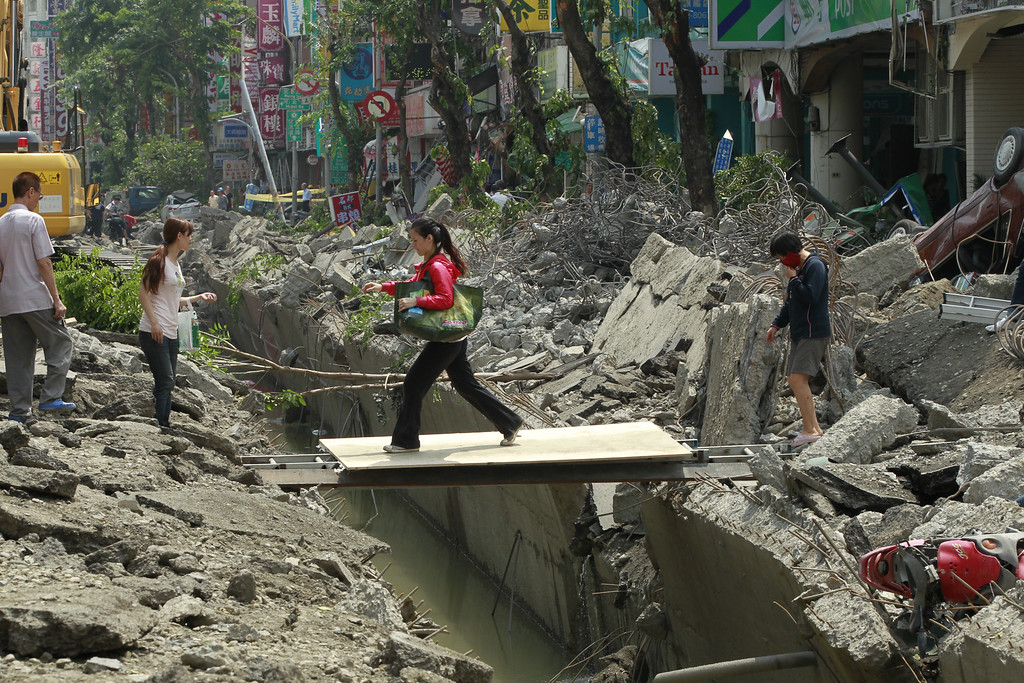 . A woman crosses over a trench made from a massive gas explosion in Kaohsiung, Taiwan, Friday, Aug. 1, 2014. Scores of people were killed and more than 200 others injured when several underground gas explosions ripped through Taiwan\'s second-largest city overnight, hurling concrete through the air and blasting long trenches in the streets, authorities said Friday. (AP Photo/Wally Santana)