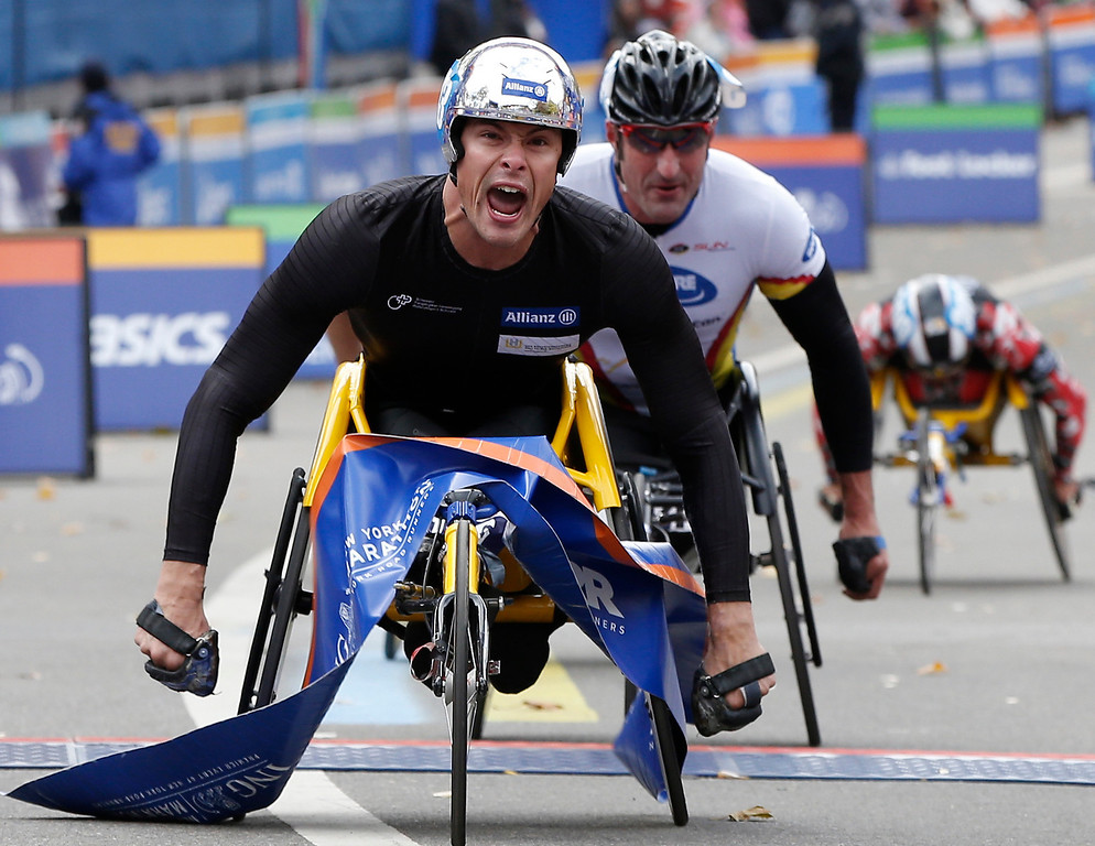 . Marcel Hug of Switzerland reacts crossing the finish line followed by Ernst Van Dyk of South Africa, center, as he wins the mens\' wheelchair division of the New York City Marathon, Sunday, Nov. 3, 2013, in New York. Person at rear right is unidentified (AP Photo/Kathy Willens)