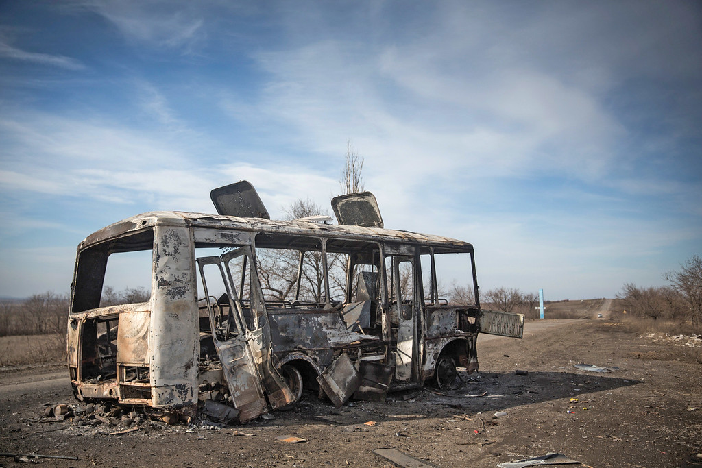. DEBALTSEVE, UKRAINE - FEBRUARY 25:  A destroyed bus sits in the middle of the road between Debaltseve and Artyomovsk on February 25, 2015 in Debaltseve, Ukraine. Ukrainian soldiers fled down this road from Debaltseve to Artyomovsk after approximately one month of fighting with Russian backed rebels on February 18. Of the town\'s 100,000 people only approximately 11,000 civilians remain in the town. Debaltseve is considered an asset to both Ukrainians and the rebels due to the railway station and it\'s connection to other eastern Ukranian towns.  (Photo by Andrew Burton/Getty Images)