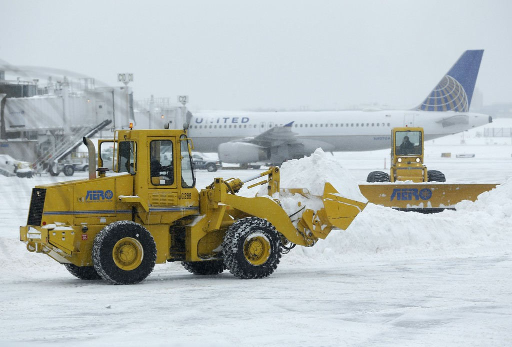 . Machines clear snow off the tarmac at LaGuardia Airport in New York, Tuesday, Jan. 27, 2015. A storm packing blizzard conditions spun up the East Coast early Tuesday, pounding parts of coastal New Jersey northward through Maine with high winds and heavy snow. (AP Photo/Seth Wenig)