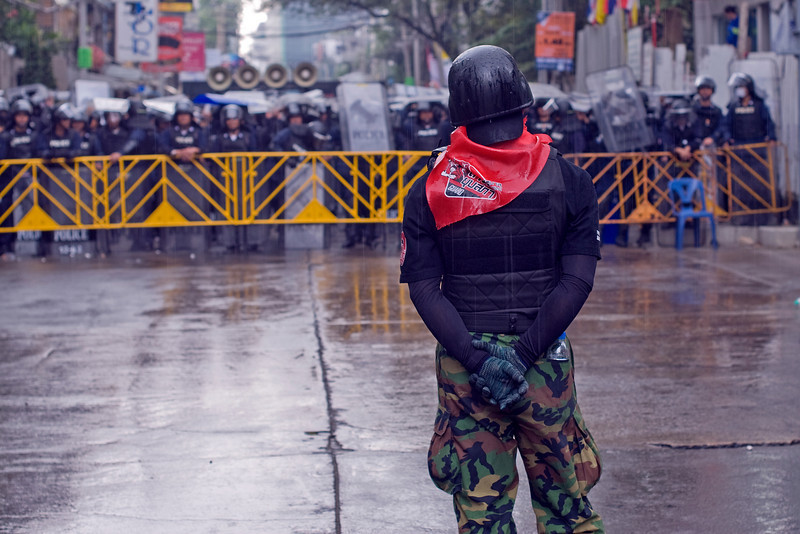 A red shirt protester in uniform stands alone in front of police
