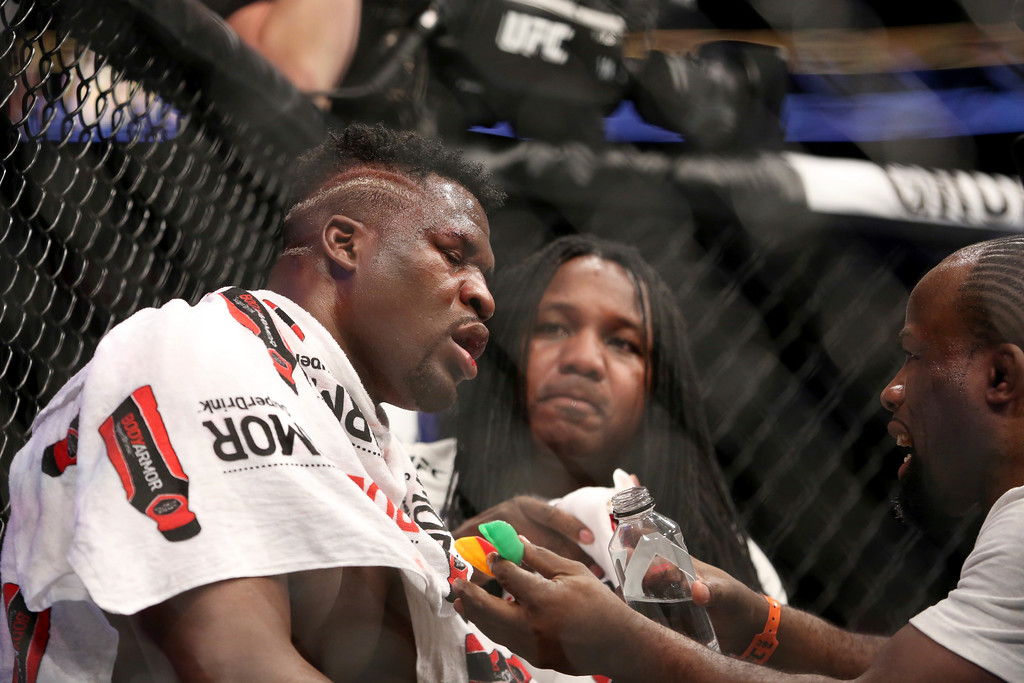 . An exhausted Francis Ngannou sits seen in his corner before the fifth round against Stipe Miocic during a heavyweight championship mixed martial arts bout at UFC 220, early Sunday, Jan. 21, 2018, in Boston. Miocic retained his title via unanimous decision. (AP Photo/Gregory Payan)