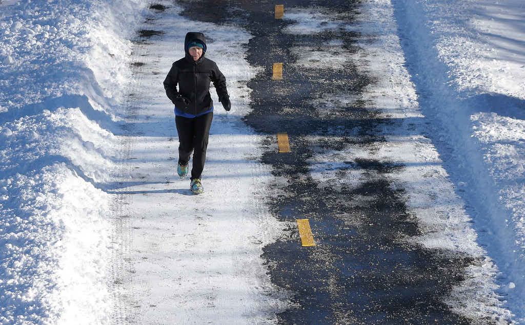. A runner makes her way along a path near the Charles River, Sunday, Jan. 8, 2017, in Boston. A storm wreaked havoc along the East Coast arrived in southern New England Saturday, making travel treacherous throughout the region. (AP Photo/Steven Senne)