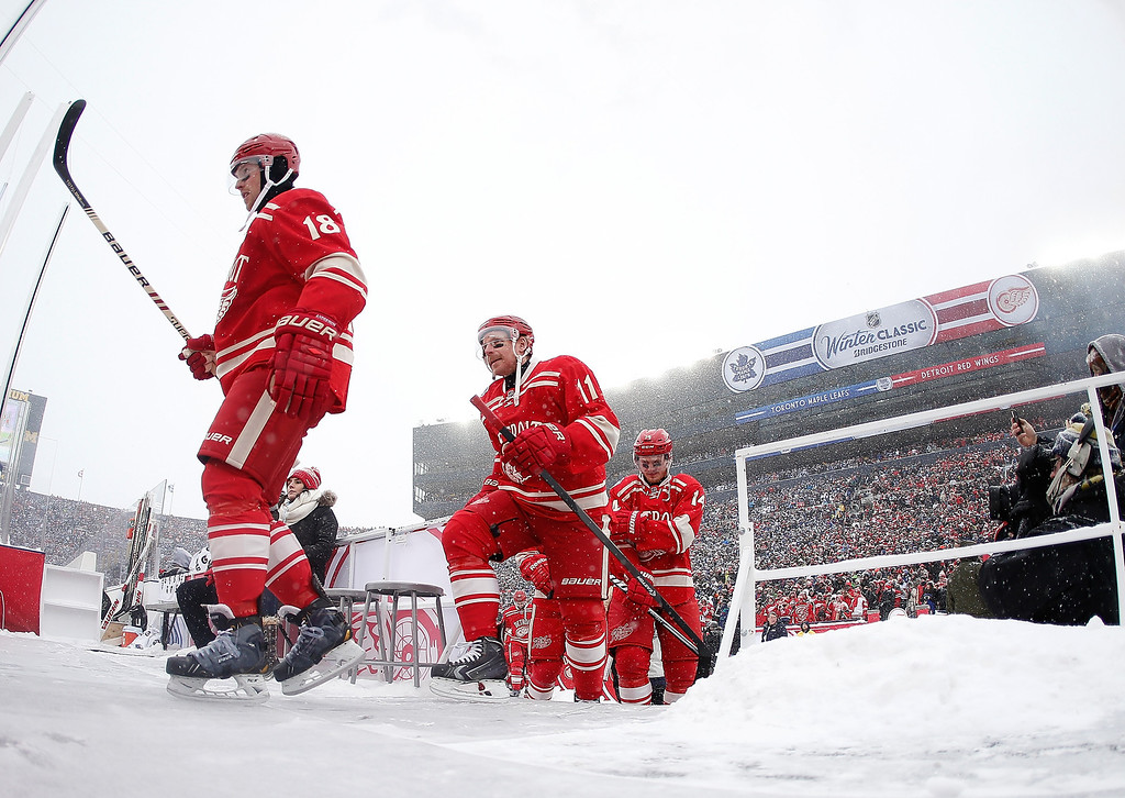 . Joakim Andersson #18, Daniel Alfredsson #11 and Gustav Nyquist #14 of the Detroit Red Wings take the ice for the 2014 Bridgestone NHL Winter Classic at Michigan Stadium on January 1, 2014 in Ann Arbor, Michigan. (Photo by Gregory Shamus/Getty Images)