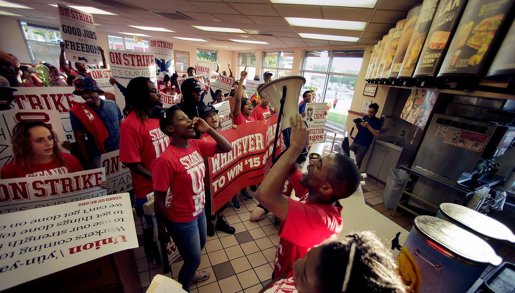 ". Protesters gather inside a Taco Bell restaurant in Kansas City, Mo. on Thursday, Sept. 4, 2014, as part of the ""Fight for $15\"" campaign, a national protest to push fast-food chains to pay their employees at least $15 an hour. The movement, which is backed financially by the Service Employees International Union and others, has gained national attention at a time when the wage gap between the poor and the rich has become a hot political issue.  (AP Photo/Charlie Riedel)"