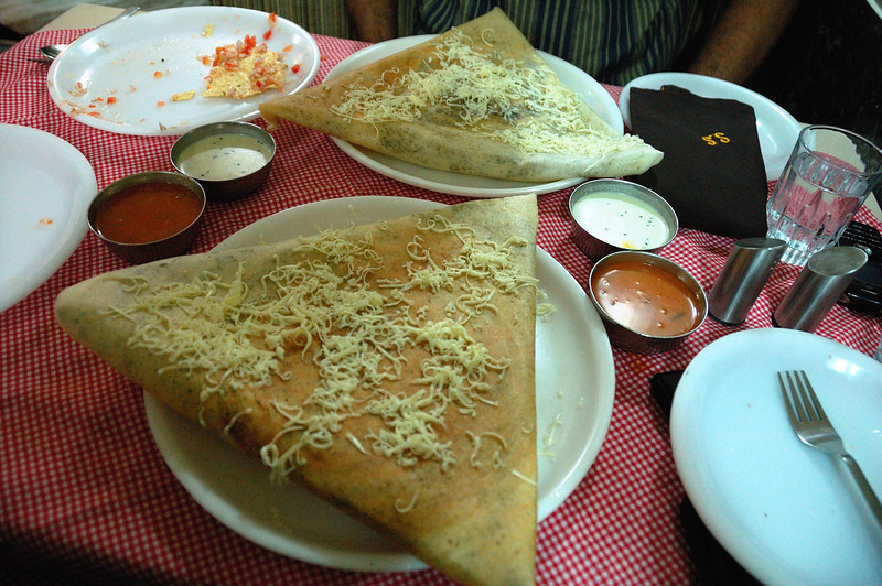 Masala Dosa (crepe made from rice and black lentils). A masala dosa is made by stuffing a dosa with a lightly cooked filling of potatoes, fried onions and spices. Top left: Veg Samosa