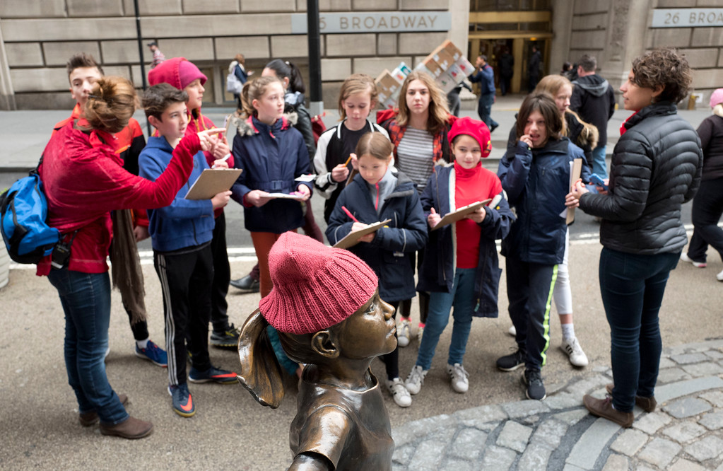 ". Sixth grade students from the Blue School draw a statue of a fearless girl, Wednesday, March 8, 2017, in New York. The statue was installed by an investment firm in honor of International Women\'s Day. An inscription at the base reads, ""Know the power of women in leadership. She makes a difference. State Street Global Advisors.\"" (AP Photo/Mark Lennihan)"