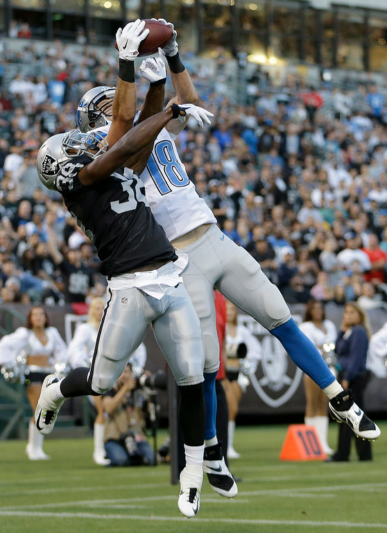 . Detroit Lions wide receiver Kris Durham (18) catches a 4-yard touchdown over Oakland Raiders cornerback T.J. Carrie (38) during the first quarter of an NFL preseason football game in Oakland, Calif., Friday, Aug. 15, 2014. (AP Photo/Ben Margot)