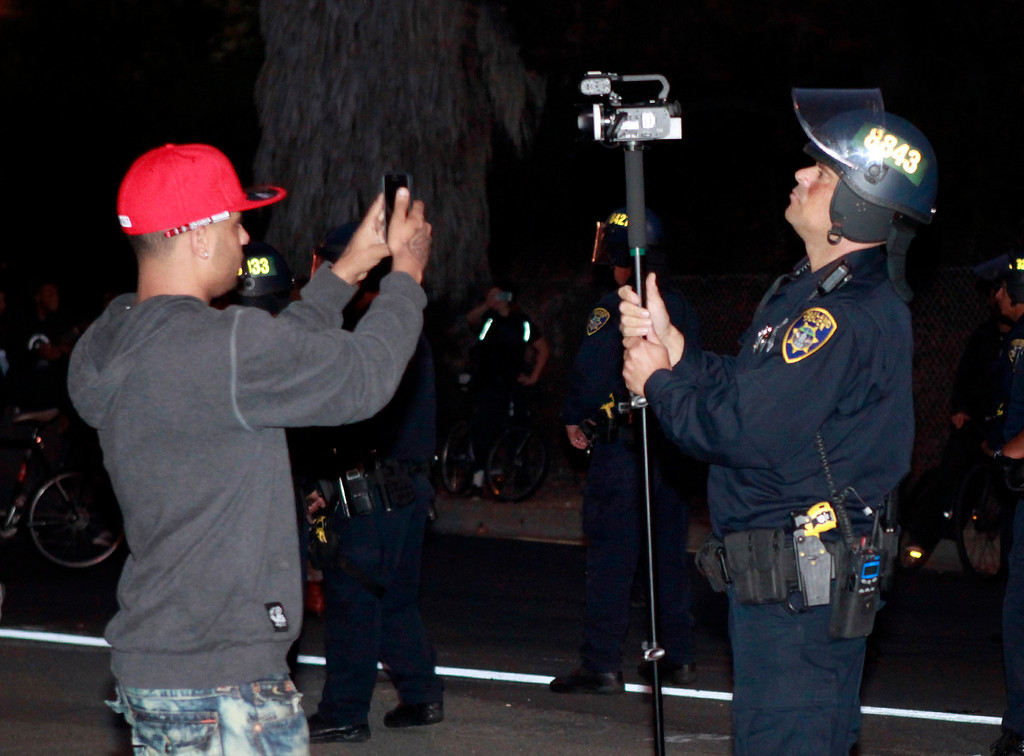 . A camera standoff between an Oakland police officer with a video camera and a protester with a cell phone camera takes place during the third day of unrest over the George Zimmerman acquittal on Monday evening, July 15, 2013 in Oakland, Calif. (Karl Mondon/Bay Area News Group)