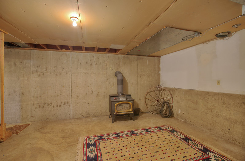 unfinished basement area with woodstove.jpg