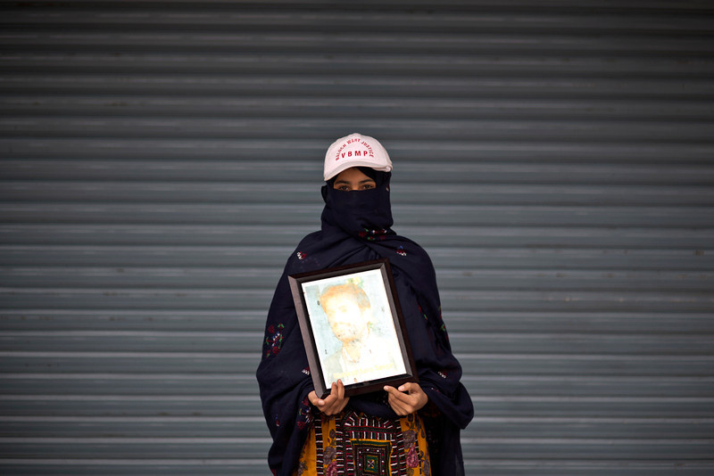 . Robi Zarmen poses for a portrait holding a photograph of her dead brother, who went missing on February 11, 2011, and a year after was reported dead, while she and other relatives take a break from a long march protest, in Rawalpindi, Pakistan, Friday, Feb. 28, 2014. She is part of a group of activists from the impoverished southwestern province of Baluchistan who walked roughly 3,000 kilometers (1,860 miles) to the capital of Islamabad to draw attention to alleged abductions of their loved ones by the Pakistani government. (AP Photo/Muhammed Muheisen)