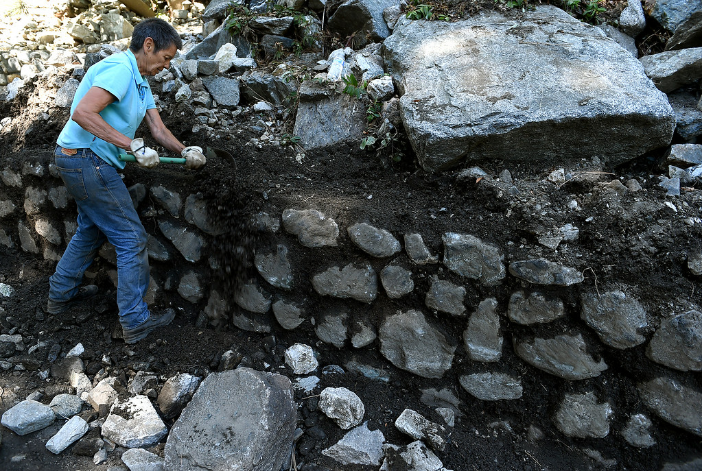 . Pat Marks removes mud and rocks from her front yard as residents continue to clean-up from Sunday\'s storm in Mt. Baldy, CA, Tuesday, August 5, 2014. (Photo by Jennifer Cappuccio Maher/Inland Valley Daily Bulletin)