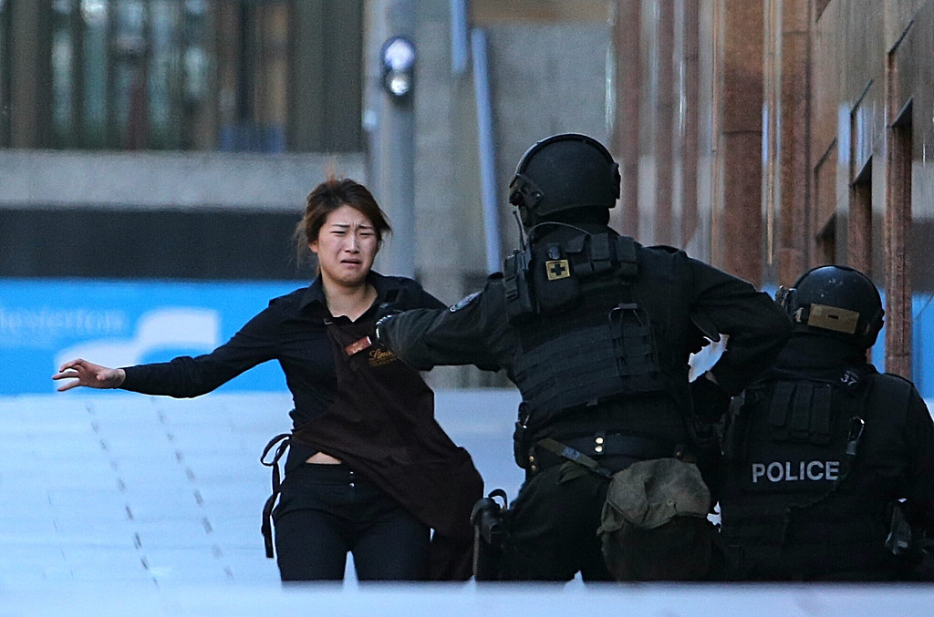 . An armed tactical response police officer grabs a hostage as she runs to flee from a cafe under siege at Martin Place in the central business district of Sydney, Australia, Monday, Dec. 15, 2014. New South Wales state police would not say what was happening inside the cafe or whether hostages were being held. But television footage shot through the cafe\'s windows showed several people with their arms in the air. (AP Photo/Rob Griffith)