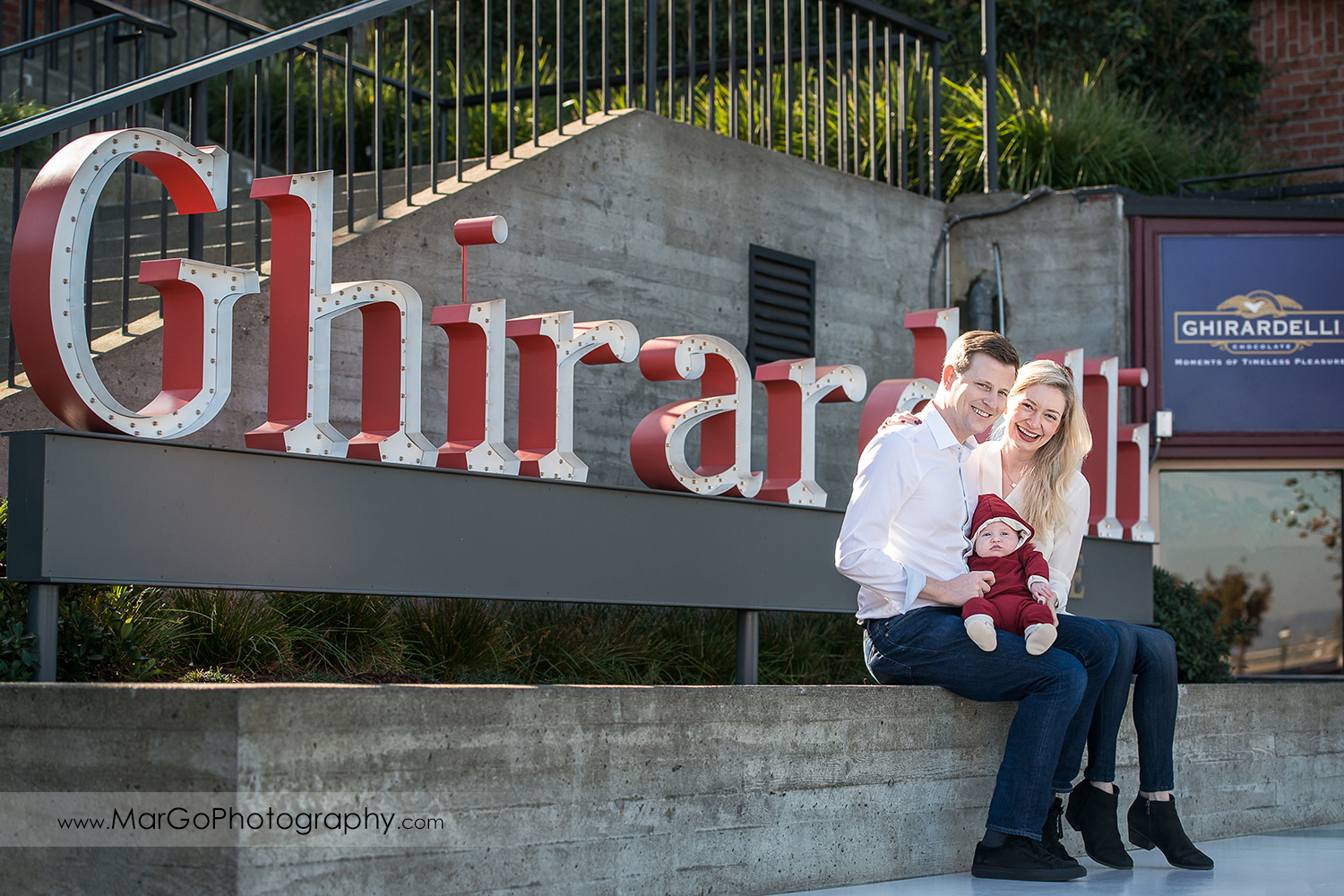 portrait of mother and father in white shirts with baby in Christmas jumpsuit sitting in front of Ghirardelli sign at San Francisco Ghirardelli Square