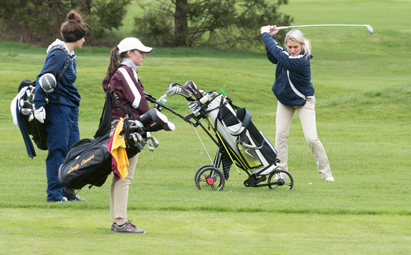 04/30/18 Wesley Bunnell | Staff Newington girls golf vs New Britain on Monday afternoon at Indian Hill Golf Club in Newington. Newington's Jessica Pierschalski, L, waits with New Britain's Cate Keithline as Newington's Chloe Bilodeau hits her second shot.