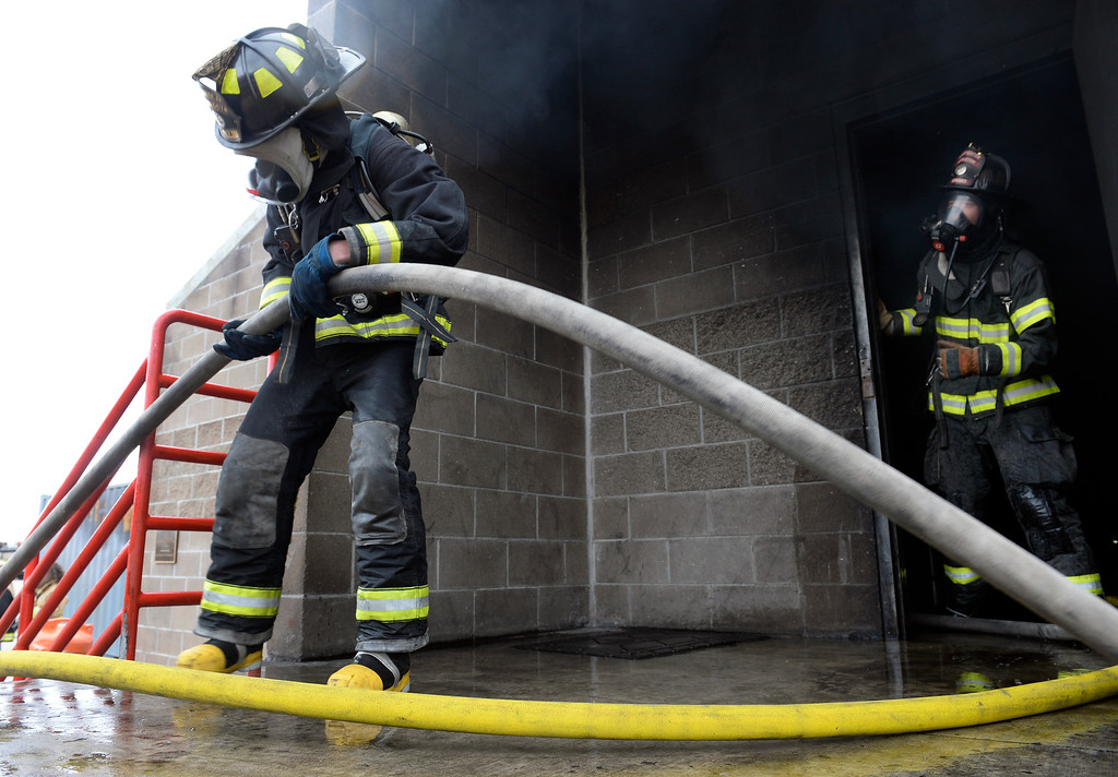 . Levi Stolba, 19, left, pulls the hose in to the smoke-filled training building. Douglas County School District students enrolled in the Fire Science program join firefighters in search and rescue and extinguishment scenarios at the South Metro Fire Rescue Training Center in Parker. The students have been training all year with the firefighters who have all volunteered their time to help train the students through this program. (Photo by Kathryn Scott Osler/The Denver Post)