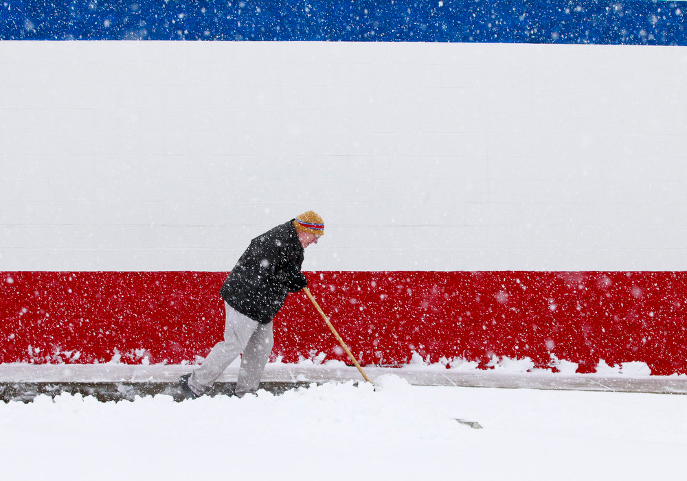 Description of . Dan Switzer, owner of the Dairy Queen on Bechtle Avenue, shovels snow although the store was closed due to the weather on Wednesday, Dec. 26, 2012, in Springfield, Ohio. (AP Photo/The Springfield News-Sun, Barbara J. Perenic)