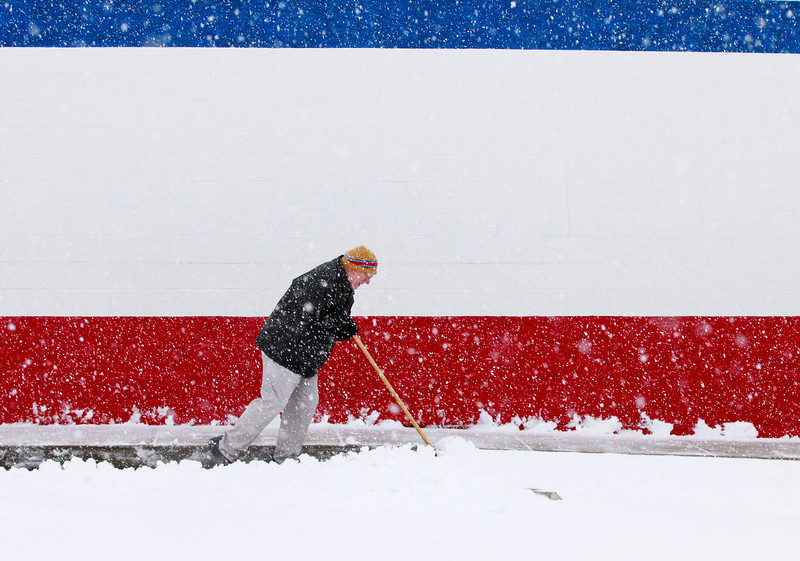 . Dan Switzer, owner of the Dairy Queen on Bechtle Avenue, shovels snow although the store was closed due to the weather on Wednesday, Dec. 26, 2012, in Springfield, Ohio. (AP Photo/The Springfield News-Sun, Barbara J. Perenic)