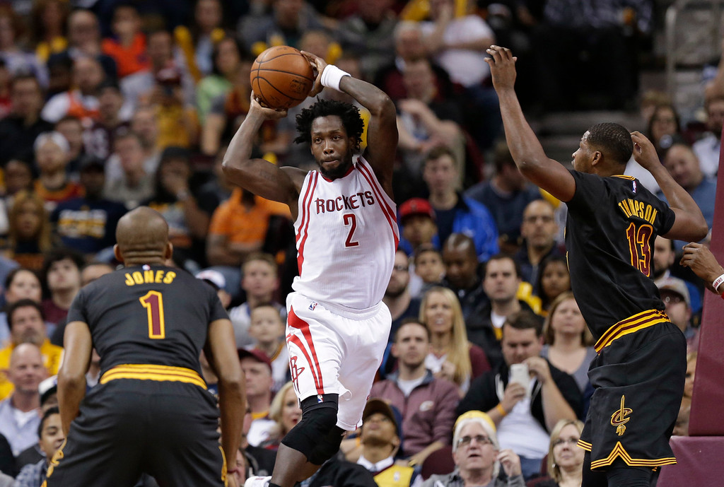 . Houston Rockets\' Patrick Beverley (2) passes over Cleveland Cavaliers\' James Jones (1) and Tristan Thompson (13) in the first half of an NBA basketball game Tuesday, March 29, 2016, in Cleveland. (AP Photo/Tony Dejak)