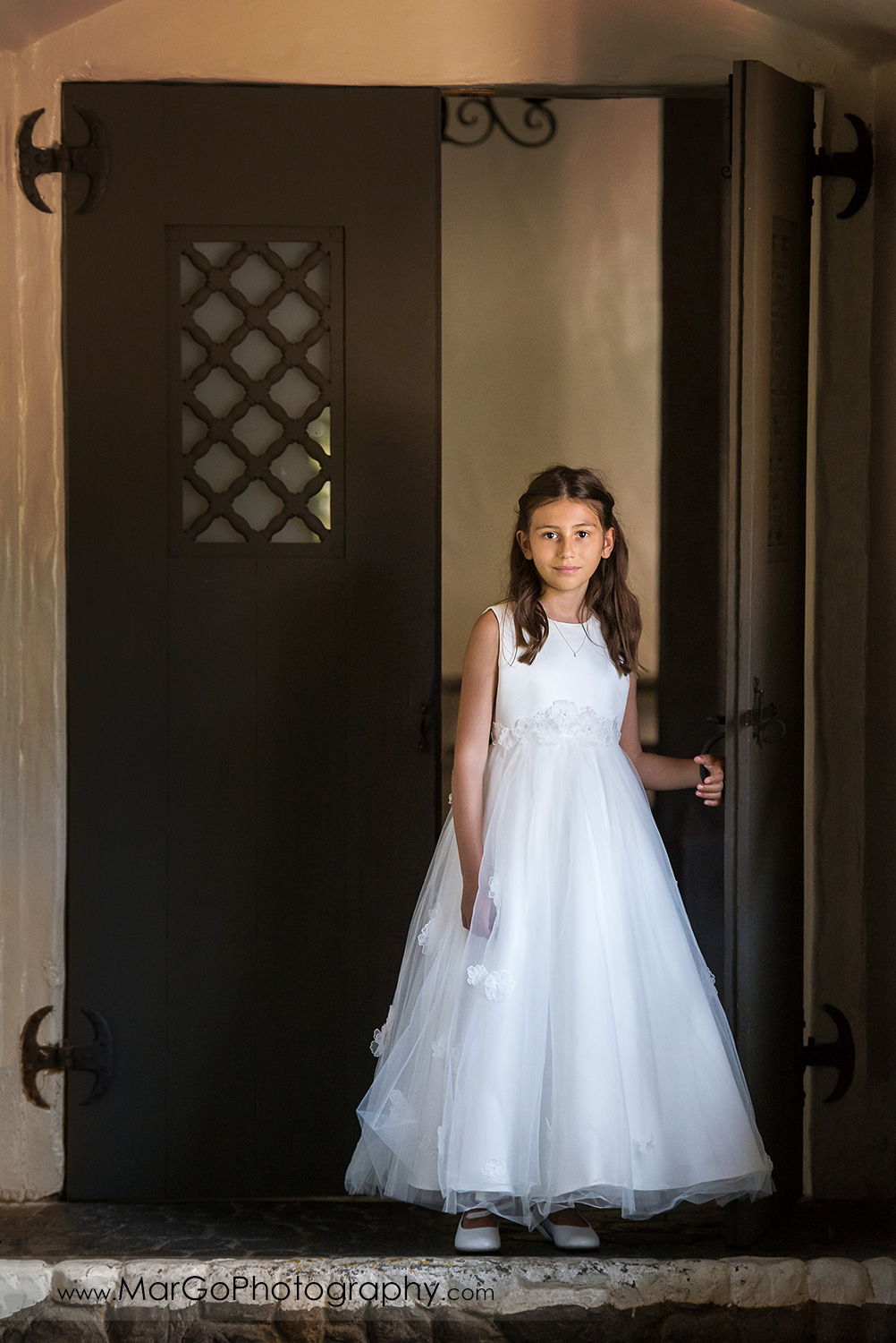 first communion girl in white dress walking through brown door at Cafe Wisteria in Menlo Park
