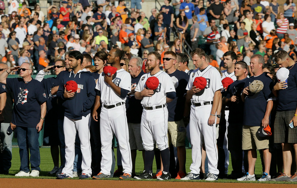 . From left to right, Detroit Tigers  pitcher Anibal Sanchez, relief pitcher Al Alburquerque, catcher Bryan Holaday and pitcher Max Scherzer stand with veterans during the national anthem before a baseball game against the Tampa Bay Rays in Detroit, Friday, July 4, 2014. (AP Photo/Carlos Osorio)