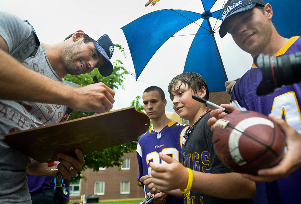 . Quarterback Christian Ponder signs autographs for soaked Vikings faithful after arriving at Vikings training camp in Mankato on Thursday, July 25, 2013. The team\'s first practice will be on Friday.  (Pioneer Press: Ben Garvin)